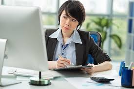 Picture of a virtual assistance in her office sitting at her desk with a computer